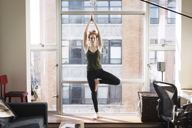 Portrait of confident woman practicing tree pose by window at home