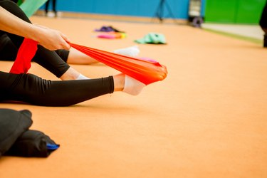 Young Rhythmic Gymnastics Athlete Stretching Legs with Resistance Band