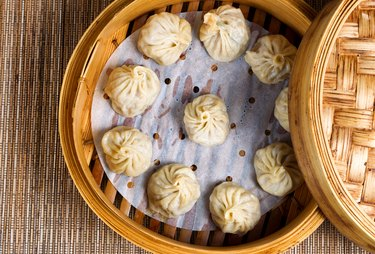 Freshly cooked dumplings inside of bamboo steamer ready to eat