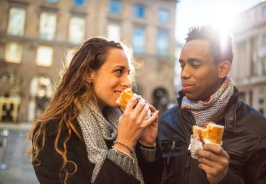 Young couple eating bread outdoors for carb diet