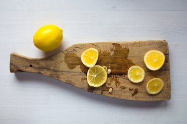 Cut lemons with seeds and lemon juice on wooden cutting board
