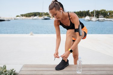 Young sporty woman fixing her shoelaces on a bench