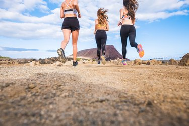 group of beautiful back view of females runners doing sport activity jogging in outdoor. mountain in background and enjoy the healthy leisure activity together. ground view and blue sky