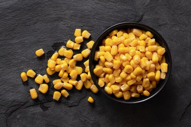 Canned sweet corn in a black ceramic bowl isolated on black slate next to spilled sweet corn. Top view.
