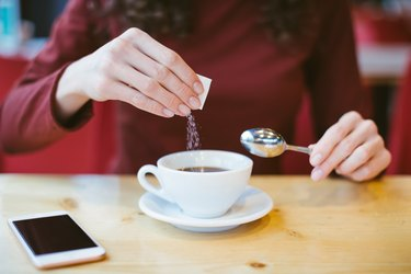 Woman's hands pouring sugar into black coffee - girl sitting at the table with espresso and smartphone - blood and glycemic index control for diabetes -excess of white sugar in food concept