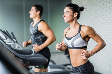 couple running in gym on treadmill