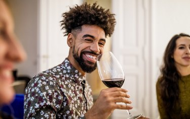 Smiling man drinking red wine during dinner party at home