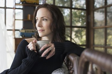 Pensive mature brunette woman drinking coffee at home