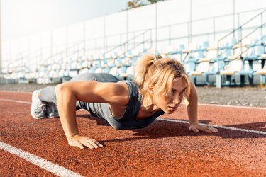 Woman cross-training outside on a track.