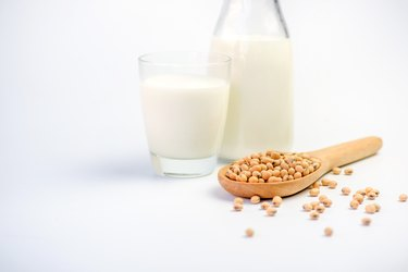 Milk with soy beans on white background