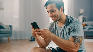 Happy Strong Athletic Fit Man in T-shirt and Shorts is Using a Mobile Phone After Morning Exercises at Home in His Spacious and Bright Living Room with Minimalistic Interior.