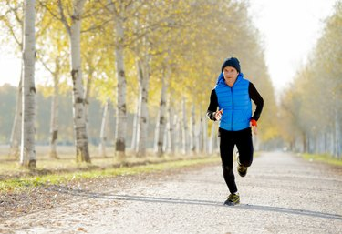 sport man running off road with trees under Autumn sunlight and wearing a running vest