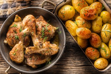 Roasted chicken legs with potatoes cumin pepper and herbs top of view