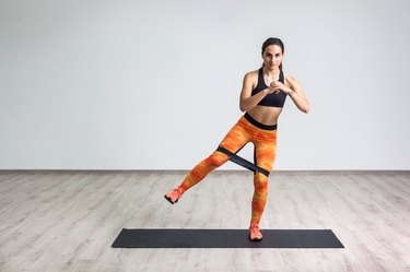 Full length portrait of young sportwoman in black top and orange leggings performs exercises for the muscles of the legs with elastic resistance band.