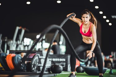 Beautiful Asian woman exercise on battling ropes training equipment in indoor fitness gym. Sport recreational activity, people workout, or healthy lifestyle concept