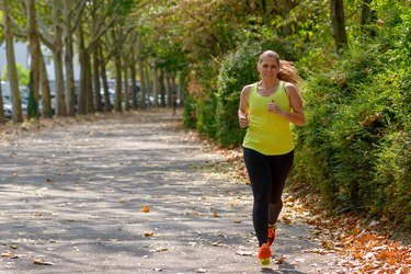 Determined middle-aged woman jogging in the park