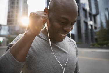Close up smiling male runner listening to music with workout headphones