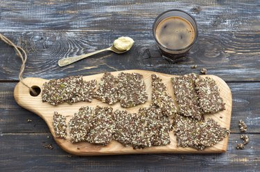 Delicious healthy multigrain gluten-free crackers, ketogenic, from chia seeds, flax, sesame and ground pumpkin seeds and keto coffee in glass with spoon of butter оn wooden table