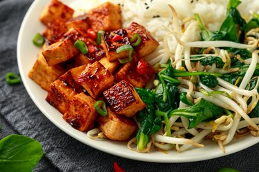 Fried Asian tofu in sweet chilli glaze served with rice, steamed spinach and beansprouts. Vegetable healthy food