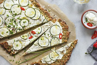Cauliflower pizza crust with zucchini, cream cheese and spring onion .