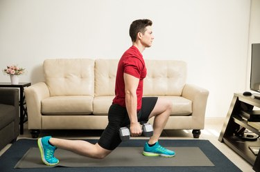 fit man wearing a red shirt and black shorts and doing a reverse lunge with dumbbells in living room
