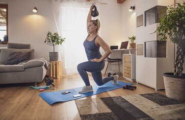 Young woman lunging with kettlebell on yoga mat in living room
