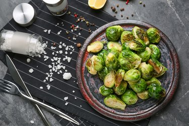 Plate with delicious roasted Brussels sprouts on table, top view
