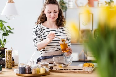 Smiling woman pouring honey in her kitchen