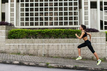 Side view of young female runner listening to music and jogging on sidewalk in town