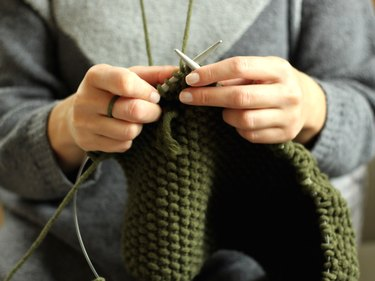 Close-up view of a woman's hands knitting