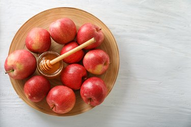 Ripe juicy apples with honey on wooden plate