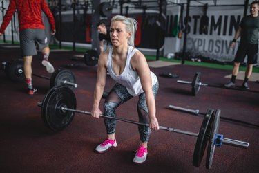 Strong woman doing deadlifts on a group training at a gym