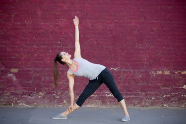 Woman doing triangle pose on the street in front of red wall
