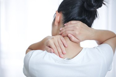 Woman with her hands around the back of her neck