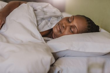 African American woman sleeping soundly in her bed at home