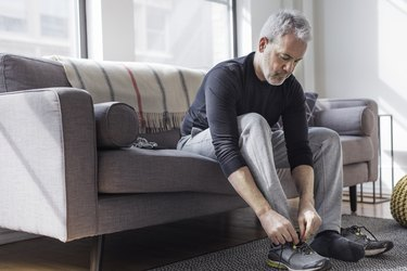 man sitting on couch tying shoes before beginner full-body worokut