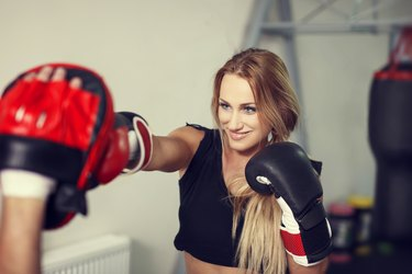 Woman boxer preparing in gym with instructor