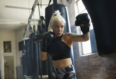 Caucasian woman hitting punching bag in gymnasium
