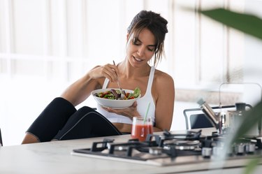 A woman at home eating salad with salad dressing, which is one of the foods bad for teeth