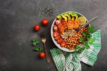 A bowl of healthy vegan and vegetarian lunch or dinner. Salad of fried chickpeas, quinoa, avocado, fried sweet potatoes and tomatoes on a dark painted background.Top view, flat lay