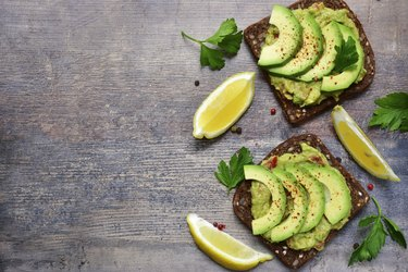 Delicious wholewheat toast with guacamole and avocado slices.