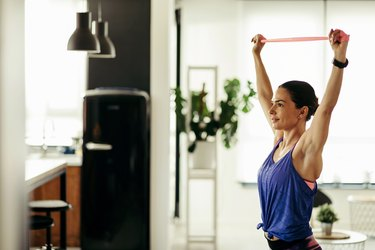 Young athletic woman using a resistance band while working out at home.