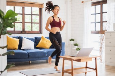 young Asian woman wearing sports bra and leggings working out at home with laptop