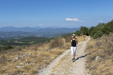 Independent solo traveler woman on the road at Dentelles de Montmirail chain of mountains in Provence in Vaucluse, France