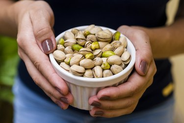 Hand holding white pot with pistachio to get the health benefits of pistachios and pistachio nutrition