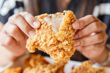 Hand holding Fried chicken and eating in the restaurant because fried eats are food that cause constipation