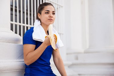 Marathon runner eating a banana as part of her diet plan