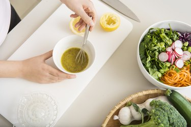 Young woman preparing a fresh salad dressing for how to season food