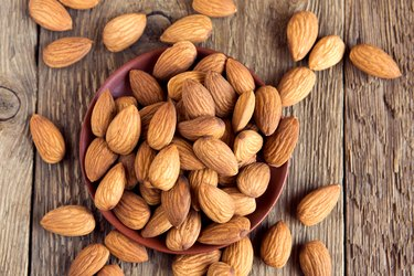 Almonds over rustic wooden background
