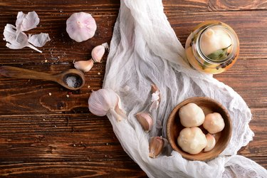 Composition with tasty fermented garlic on wooden table